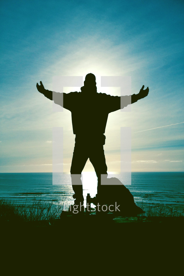 Silhouette of a man standing with outreached arms at the ocean with an aura of light around him.