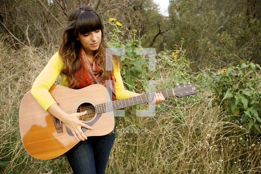 woman playing her guitar outdoors