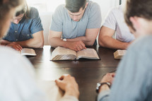 men reading Bibles and praying at a Bible study.