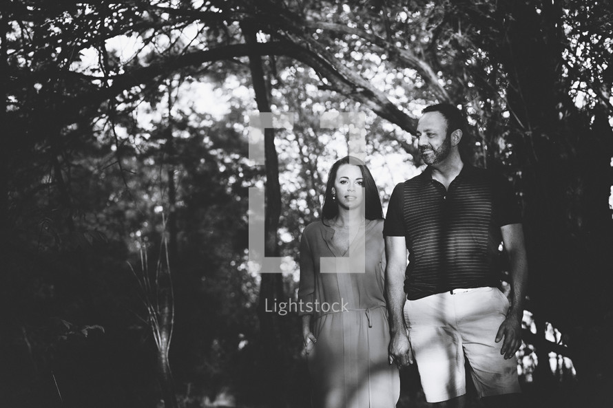 couple holding hands standing in a forest
