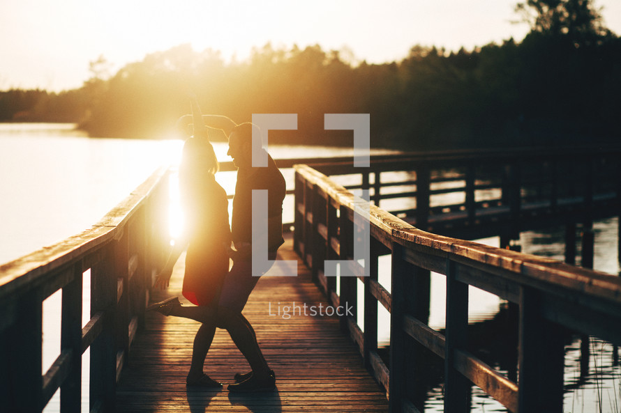 a couple dancing on a pier