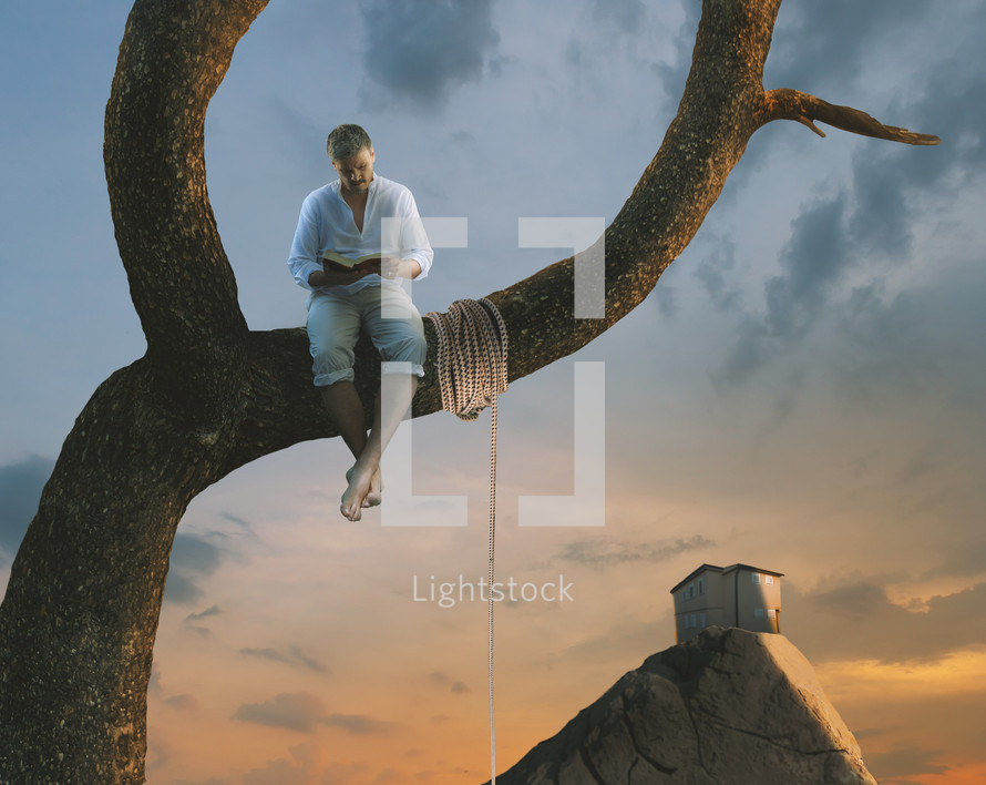 a man reading a Bible sitting on a tree branch next to a rope