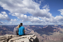 a couple snuggling at the top of a canyon