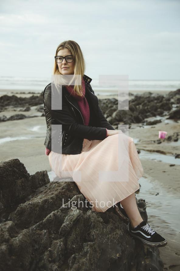 a woman sitting on a rock on a beach
