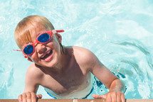 boy child in a swimming pool with goggles
