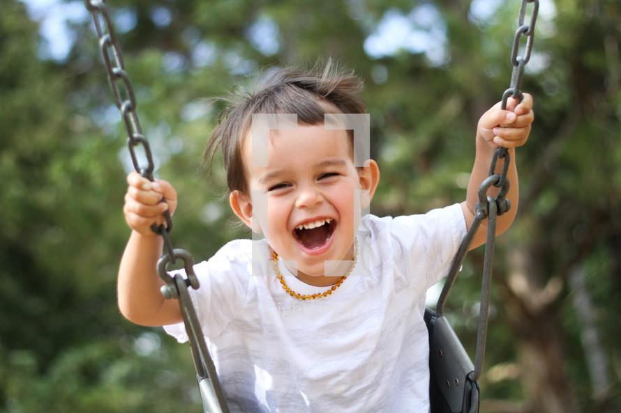 boy child swinging on a swing