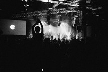 Silhouette of audience with arms raised at a worship concert.