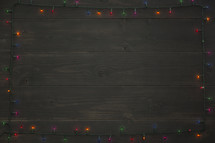 wood background with border of colored Christmas lights.