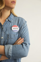 "A woman with arms crossed wearing a denim shirt and a ,""Vote,"" button."