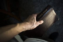 man's arm holding a Bible at his side