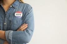 """A woman in a denim shirt wearing a red, white and blue button reading, """"Vote."""""""