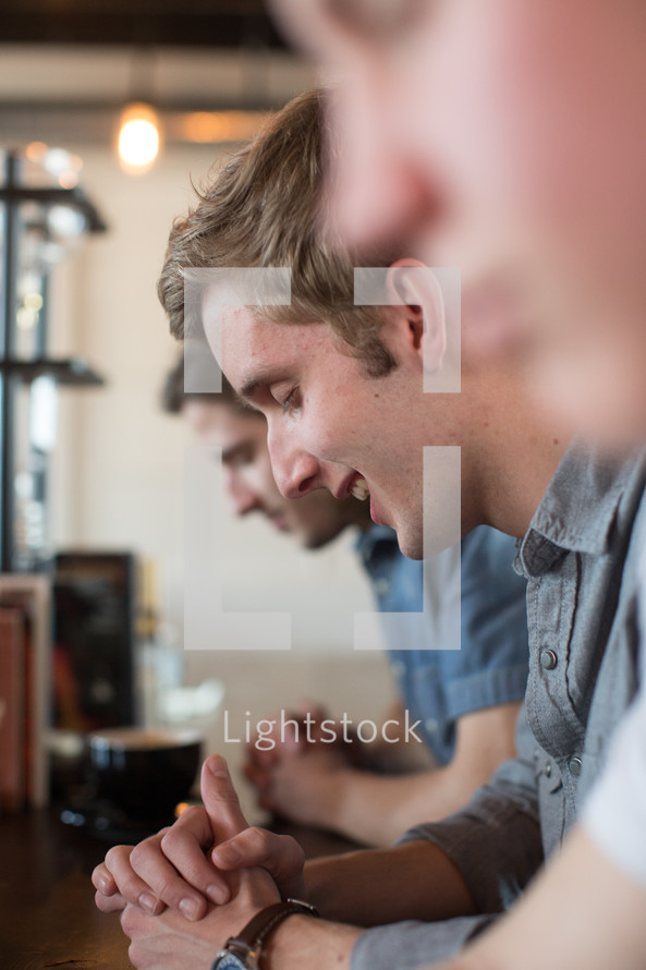 men's prayer group in prayer at a coffee shop
