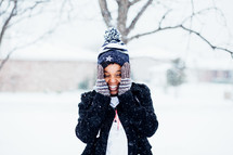 A smiling girl in the snow with her hands to her face.
