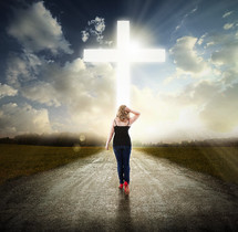 Woman walking in the middle of the road toward the light of Christ.