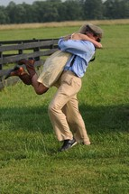 a reunited couple hugging in a pasture
