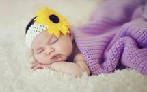 a newborn girl sleeping under a blanket