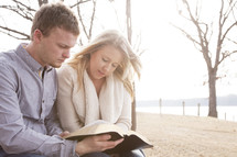 young couple reading a Bible together outdoors