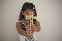 a girl holding up a crucifix