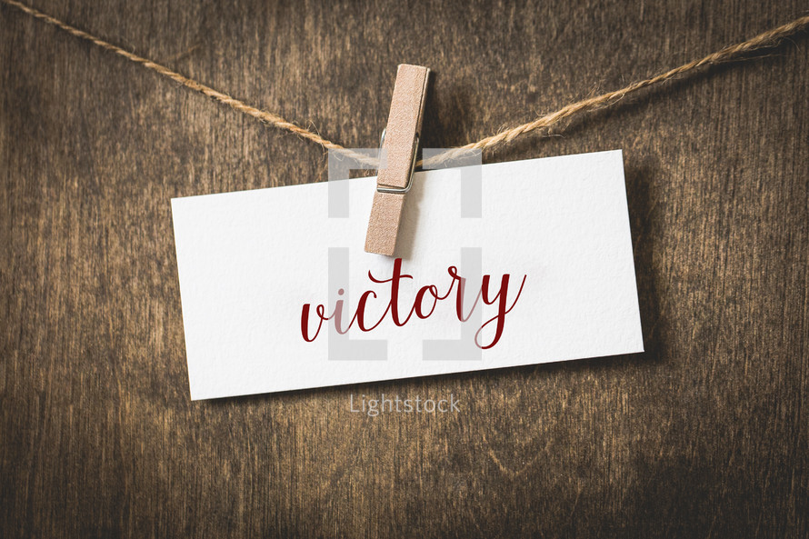word victory on white card stock hanging from a clothespin on a clothesline