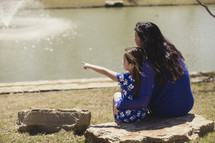 mother and daughter sitting on a rock looking out at a pond