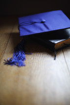 a mortar board and Bible on table