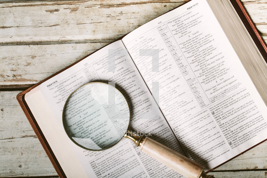 Magnifying glass on pages Bible open to Psalm 119.