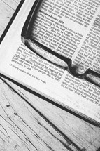 Reading glasses on top of pages of Bible open to Luke 18.