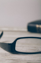 single lens of a pair of reading glasses and a Bible