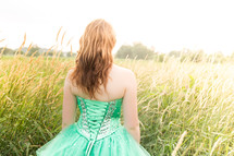 girl in a green prom dress in a field