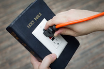 power of scripture - Bible with an outlet and power cord plugged in
