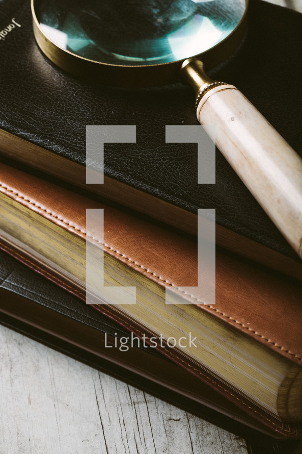 Magnifying glass on top of stack of missals and Bible laying on wooden table.