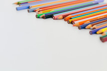 row of colored pencils on a white background