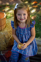smiling toddler girl holding an apple