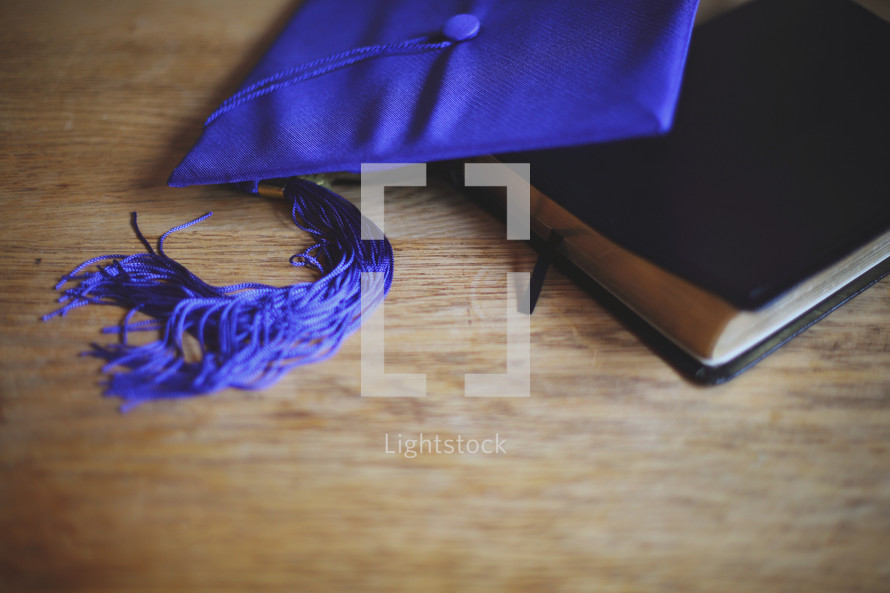 a graduation cap lays on top of a Bible