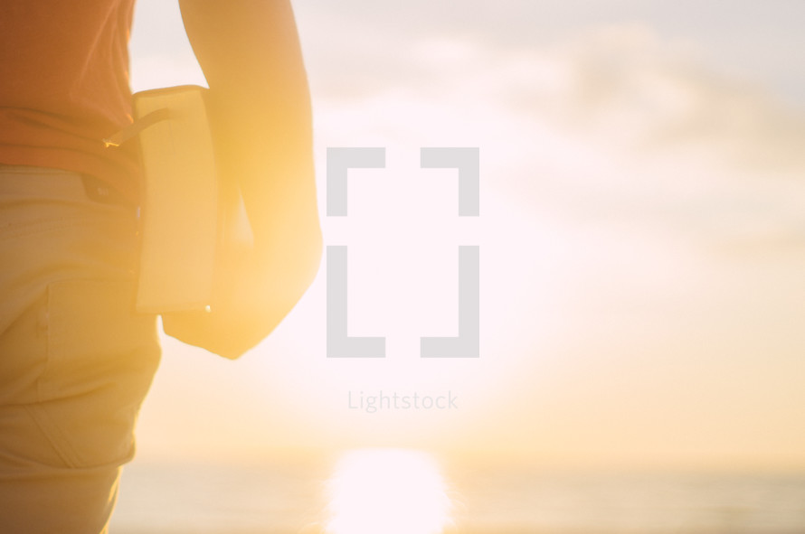 man standing on a beach holding a Bible at his side under intense sunlight