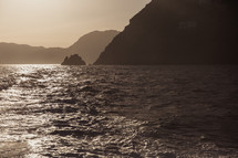 sunlight on the water and cliffs along an Italian shoreline