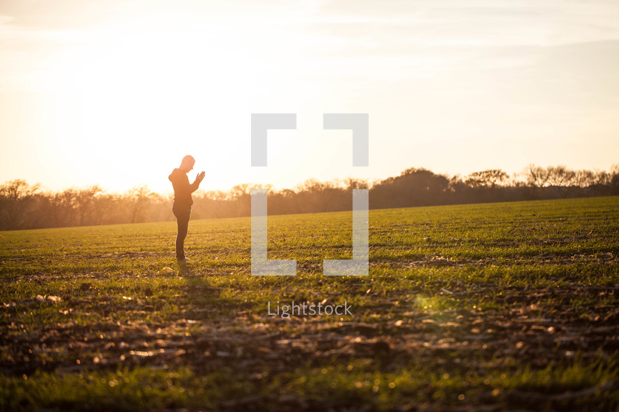 silhouette of a man praying in a field glowing under sunlight