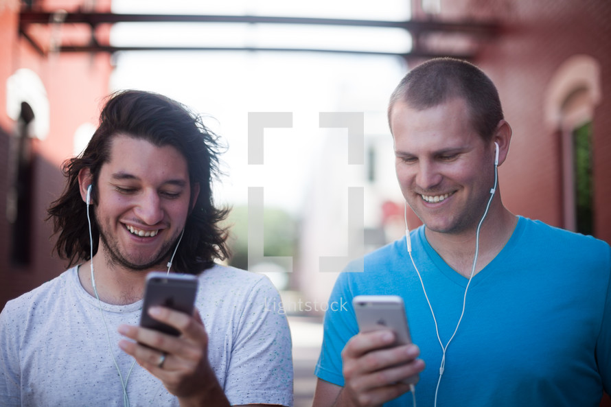 friends standing in an alley listening to a podcast