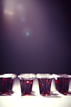 A light shins on several rows of communion cups filled with wine