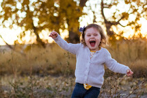 happy toddler girl running outdoors