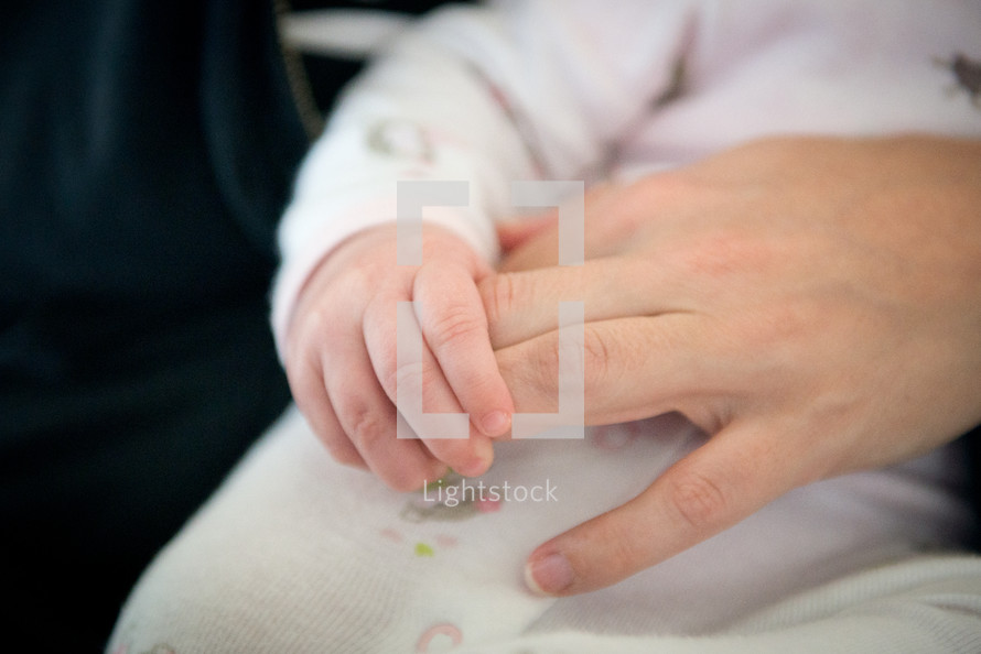 infant holding mother's hand