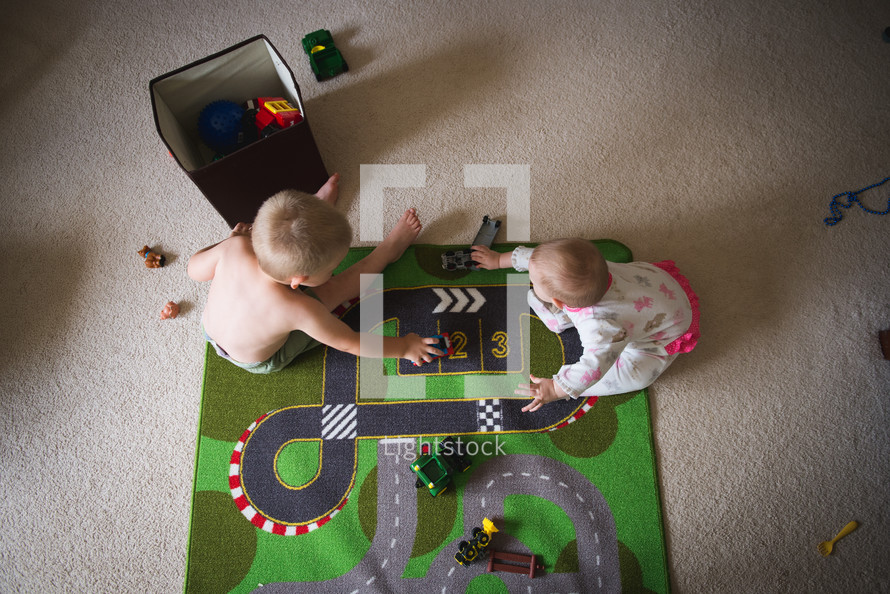 a toddler and infant playing with toys on the floor
