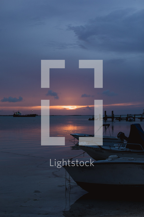 boats on a shore at sunset in the Bahamas
