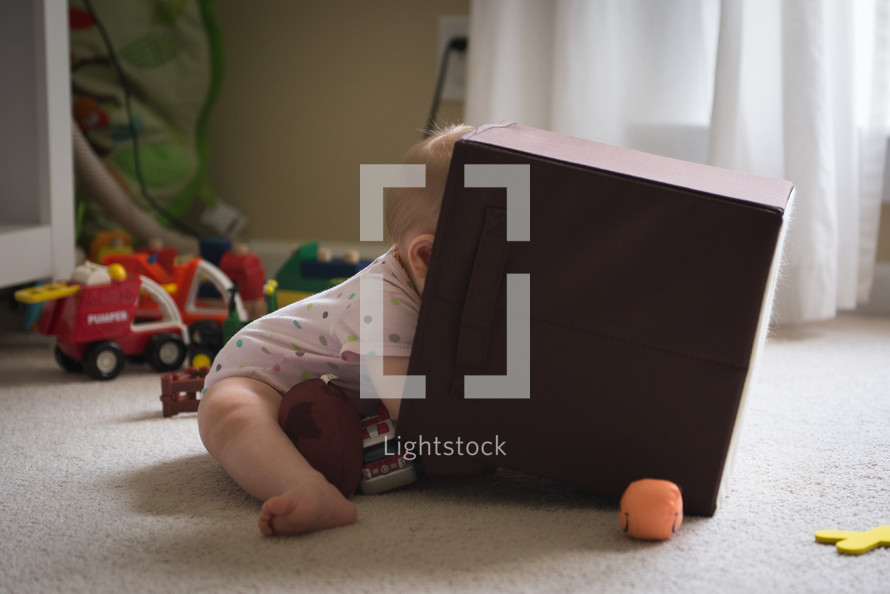 infant sitting on the floor playing with toys