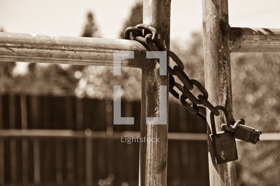 A gate chained with an old rusty chain and locks. Sepia tone.