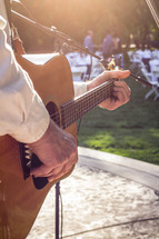 Hands strumming a guitar at an outdoor festival.