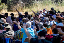 an outdoor prayer service, people with hands raised