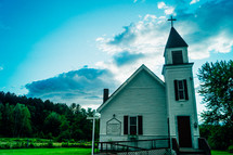a rural white church with a steeple