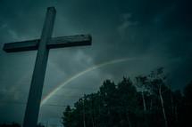 cross and rainbow under gray skies