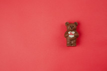 A chocolate bear holding a Valentine heart on a red background.